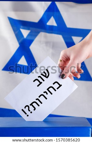 Israeli woman votes on election day. Hebrew text elections again on voting paper over Israel flag background. Israel moves closer to third elections after fails to form government. #1570385620