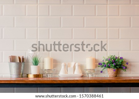 the plastic flowers, white candle, spice container and tissue paper on the wooden table with brick wallpaper as the background. #1570388461