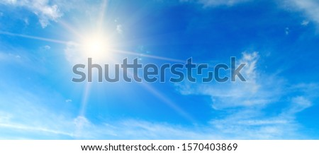 Clouds in the blue sky. Bright midday sun illuminates the space. Wide photo . #1570403869