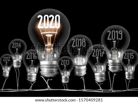 Group of shining and dimmed light bulbs with fibers in 2020, 2019, 2018... shape isolated on black background. New Year concept. #1570409281