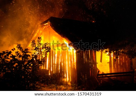 Wooden house or barn burning on fire at night. #1570431319
