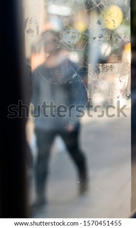 Street abstract - pedestrian walking down the street - taken through a window creating a painterly aesthetic.  #1570451455