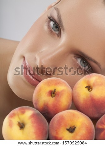 Portrait of young woman with peaches, studio shot #1570525084