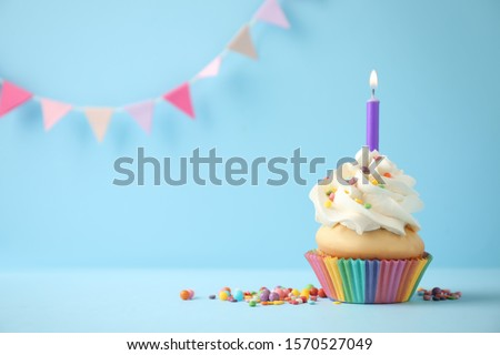 Delicious birthday cupcake with candle on light blue background. Space for text #1570527049