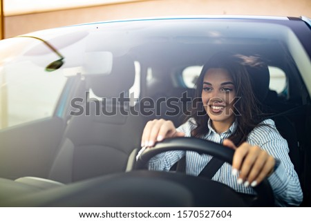 Beautiful Smiling woman driving car, attractive girl sitting in automobile, outdoors summer portrait. Young woman driving her car. Young woman in car driving seat looking ahead, close up #1570527604