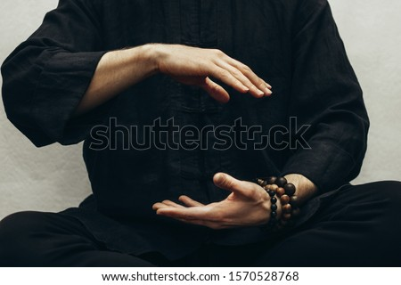 A man in black shirt sitting and doing qigong. Hands direct energy. Prayer, gratitude.Practicing monk. Qi energy. Yoga pose. Healing retreats. Close up. Royalty-Free Stock Photo #1570528768