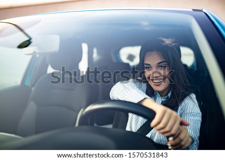 Beautiful young happy smiling woman driving her new car at sunset. Young woman driving a car in the city. Portrait of a beautiful woman in a car, looking out of the window and smiling.  #1570531843