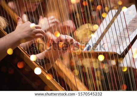 Harp player during a classical concert music, close-up. Royalty-Free Stock Photo #1570545232