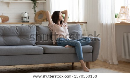 Serene lady housewife lounge sit on sofa feel fatigue napping hold hands behind head, calm young woman rest on comfort couch with eyes closed breath fresh air in cozy clean modern living room at home #1570550158