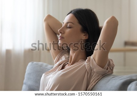 Calm tired young woman attractive face lounge leaning on sofa napping with eyes closed at home, serene lady hold hands behind head relaxing breathing fresh air sit on comfortable couch in living room Royalty-Free Stock Photo #1570550161