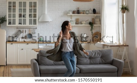 Carefree happy single young attractive woman dancing alone in modern kitchen interior, independent active lady having fun at clean home listening music enjoying freedom weekend time lifestyle at home #1570550191