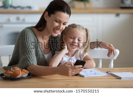Happy family mum and cute little kid daughter enjoy lifestyle hobbies using mobile app on phone look at cellphone at home, smiling mother with child girl having fun with phone sit at kitchen table