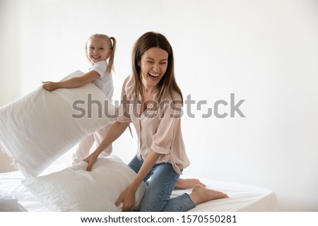 Carefree young adult mom enjoying playing weekend game fighting pillows with funny small daughter on bed, happy active family mother and cute little kid laugh having fun relax on morning leisure time