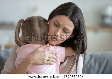 Worried young foster care parent mother comforting solacing embrace adopted little child daughter give care and protection at home, loving concerned adult mom hug sad small girl consoling kid concept #1570550326