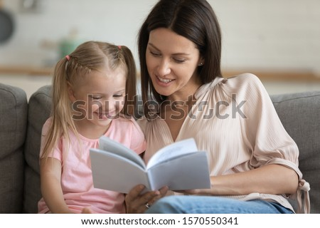 Caring single parent young adult mother and happy cute little preschool child daughter reading book learning education fairy tale story bonding enjoying family lifestyle hobby at home sit on sofa #1570550341