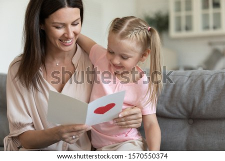 Adorable little kid daughter embracing happy young adult mom reading mothers day postcard, smiling mommy holding greeting card with red heart and congratulation from child sit in living room on couch