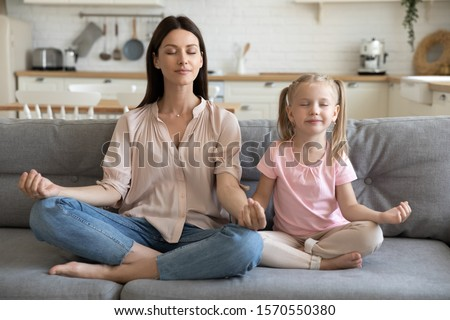 Healthy young adult parent mother and little child daughter doing yoga exercise sit on sofa at home, calm mom teaching cute small kid girl learning practice family meditation relax together concept #1570550380