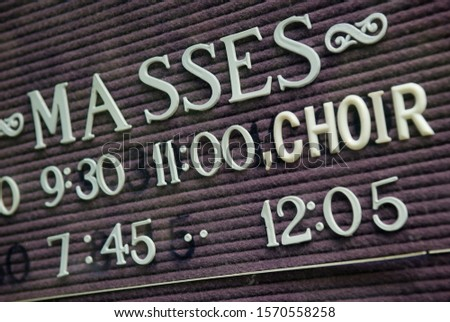 Close up of church sign listing times for masses and choir in old-fashioned white letters on faded black felt letterboard #1570558258