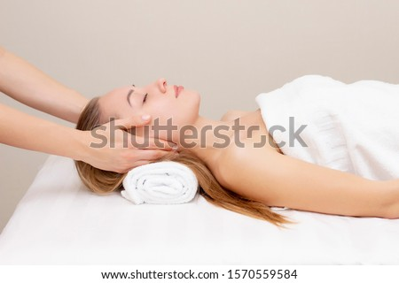 Young woman enjoying massage in spa salon. Face massage. Closeup of young woman getting spa massage treatment at beauty spa salon.Spa skin and body care. Facial beauty treatment.Cosmetology.  #1570559584