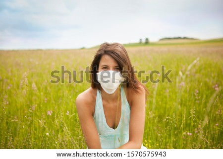 Portrait of young woman wearing face mask in field #1570575943