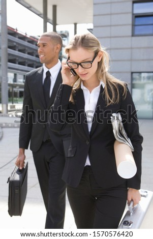 Young businesswoman on phone walking with colleague outdoors #1570576420