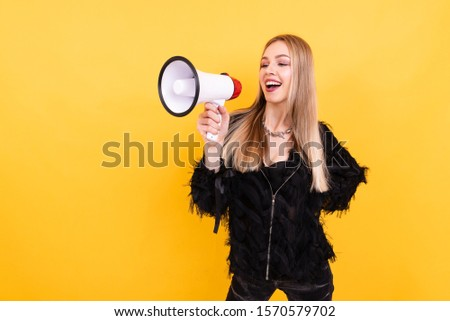 Portrait of young beautiful girl on yellow background, woman shouting into megaphone, studio portrait. People sincere emotions lifestyle concept. #1570579702