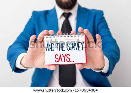Word writing text And The Survey Says. Business concept for doing poll and bring the results discuss with others Man holds empty paper with copy space in front of him Copy Space. #1570634884