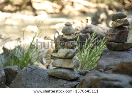 Stack of rocks along creek with cool tranquil water in background #1570645111