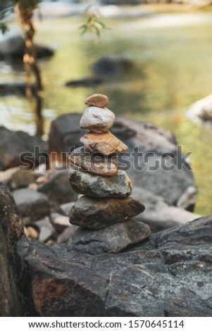 Stack of rocks along creek with cool tranquil water in background #1570645114