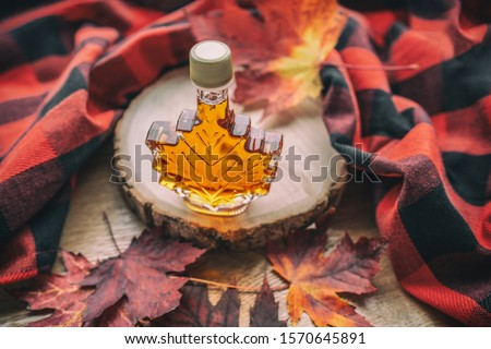 Maple syrup gift bottle in red maple tree leaves for tourist souvenir. Canada grade A amber sweet natural liquid from Quebec sugar shack maple trees farm. Royalty-Free Stock Photo #1570645891