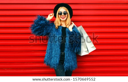 Portrait stylish smiling woman with shopping bags wearing blue faux fur coat, black round hat and sunglasses posing over red wall background #1570669552