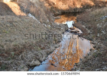 A creek with water reflecting some orange trees on a November day. Picture taken in St. Peters, Missouri.