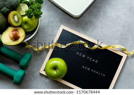 New Year for New Healthy 2020.  Fresh vegetable salad and healthy food for sport equipment fitness for women diet slimming weight loss on wood background. Healthy nutrition and health care Concept #1570678444