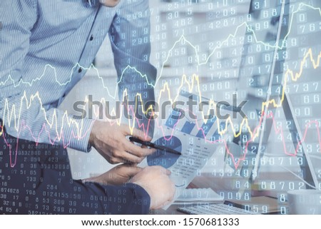 Double exposure of chart with businessman typing on computer in office on background. Concept of hard work. #1570681333