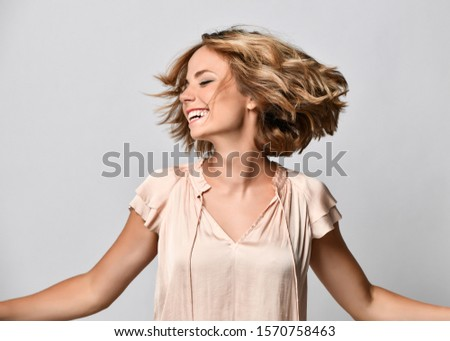 young woman in a beige short-sleeved satin blouse shakes her head with her hair. The concept of joy, happiness, joy, fun #1570758463