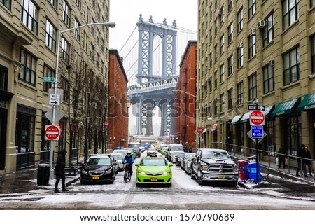 Manhattan Bridge during winter snowstorm blizzard in New York City with heavy snow falling, cars covered by snow and people commuting during snow storm. Manhattan, New York USA January 6, 2015 #1570790689