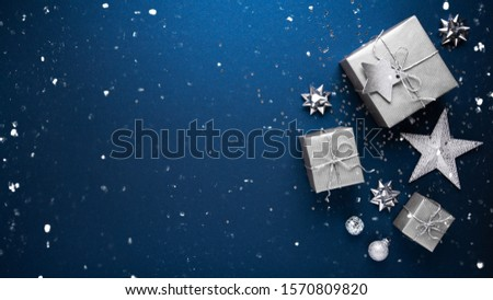 Merry Christmas and Happy Holidays greeting card, frame, banner. New Year. Noel. Silver Christmas gifts, ornaments on blue background top view. Winter holiday xmas theme. Flat lay. #1570809820