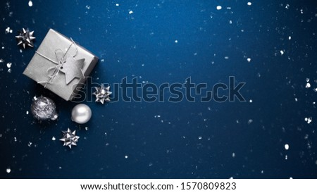 Merry Christmas and Happy Holidays greeting card, frame, banner. New Year. Noel. Silver Christmas gifts, ornaments on blue background top view. Winter holiday xmas theme. Flat lay. #1570809823