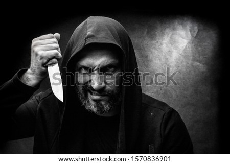 Black and white portrait of a bald bearded man in a hood on a dirty gray background. Maniac with a knife concept. #1570836901