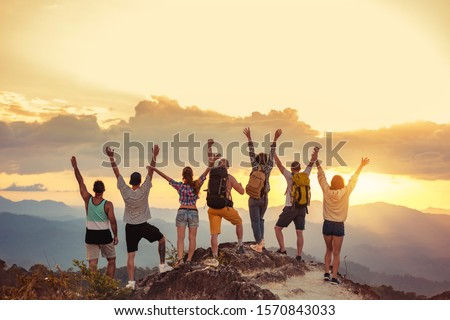 Group of happy friends stands with raised arms at sunset mountain and enjoys sunset #1570843033