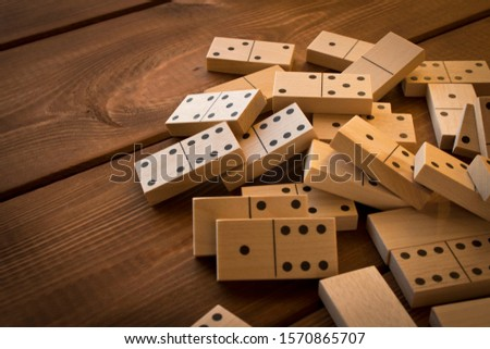 Playing dominoes on a wooden table. Leisure games concept. Domino effect #1570865707