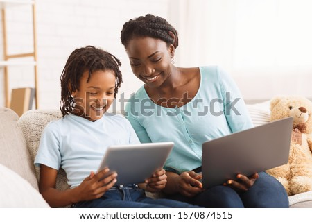 Black Mother Helping Daughter With Homework, Studying Together Using Digital Tablet And Laptop