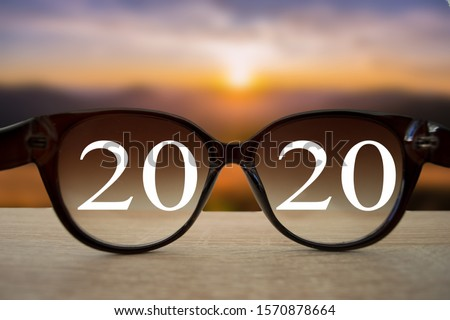2020 white text with black eye glasses on wooden table over blur autumn landscapes. Business vision happy new year. Royalty-Free Stock Photo #1570878664
