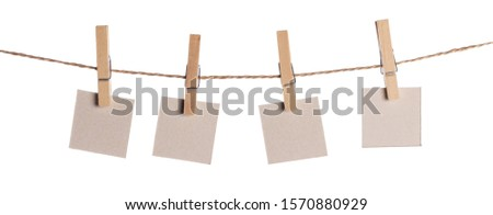 Set of four blank paper notes held on a string with clothespins isolated on white background #1570880929