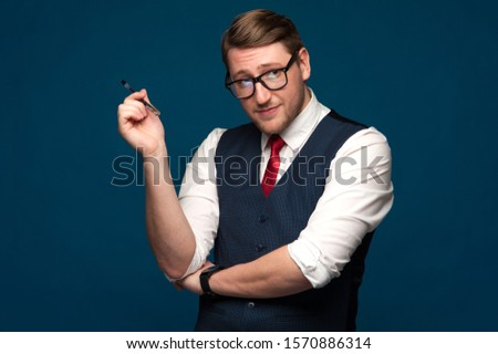 Portrait of nerdy hipster man in blue jacket and red tie holding a pen looking at the camera. Office manager in big glasses holding a pen on blue background in studio