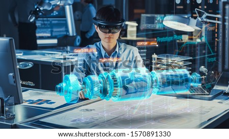 Industrial Factory Chief Engineer Wearing AR Headset Designs a Prototype of an Electric Motor on the Holographic Projection Blueprint. Futuristic Virtual Design of Mixed Technology Application. #1570891330