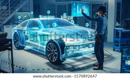 Automotive Engineer Use Virtual Reality Headset for Virtual Electric Car 3D Model Design Analysis and Improvement. 3D Graphics Visualization Shows Fully Developed Vehicle Prototype Analysed, Optimized #1570892647