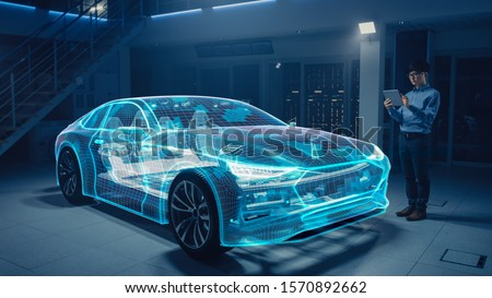 Automotive Engineer Working on Electric Car Chassis Platform, Using Tablet Computer with Augmented Reality 3D Software. Futuristic Atomative Facility: Virtual Design with Mixed Technology Application. Royalty-Free Stock Photo #1570892662