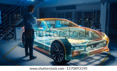 In Automotive Innovation Facility Automobile Design Engineer Working on 3D Holographic Model Projection of Electric Car. Futuristic Concept of Virtual and Augmented Realty Use. #1570893190