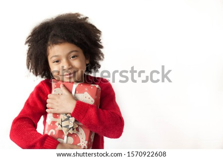 Festive Christmas concept. Happy adorable african american child girl with christmas gift in hands isolated on white background.